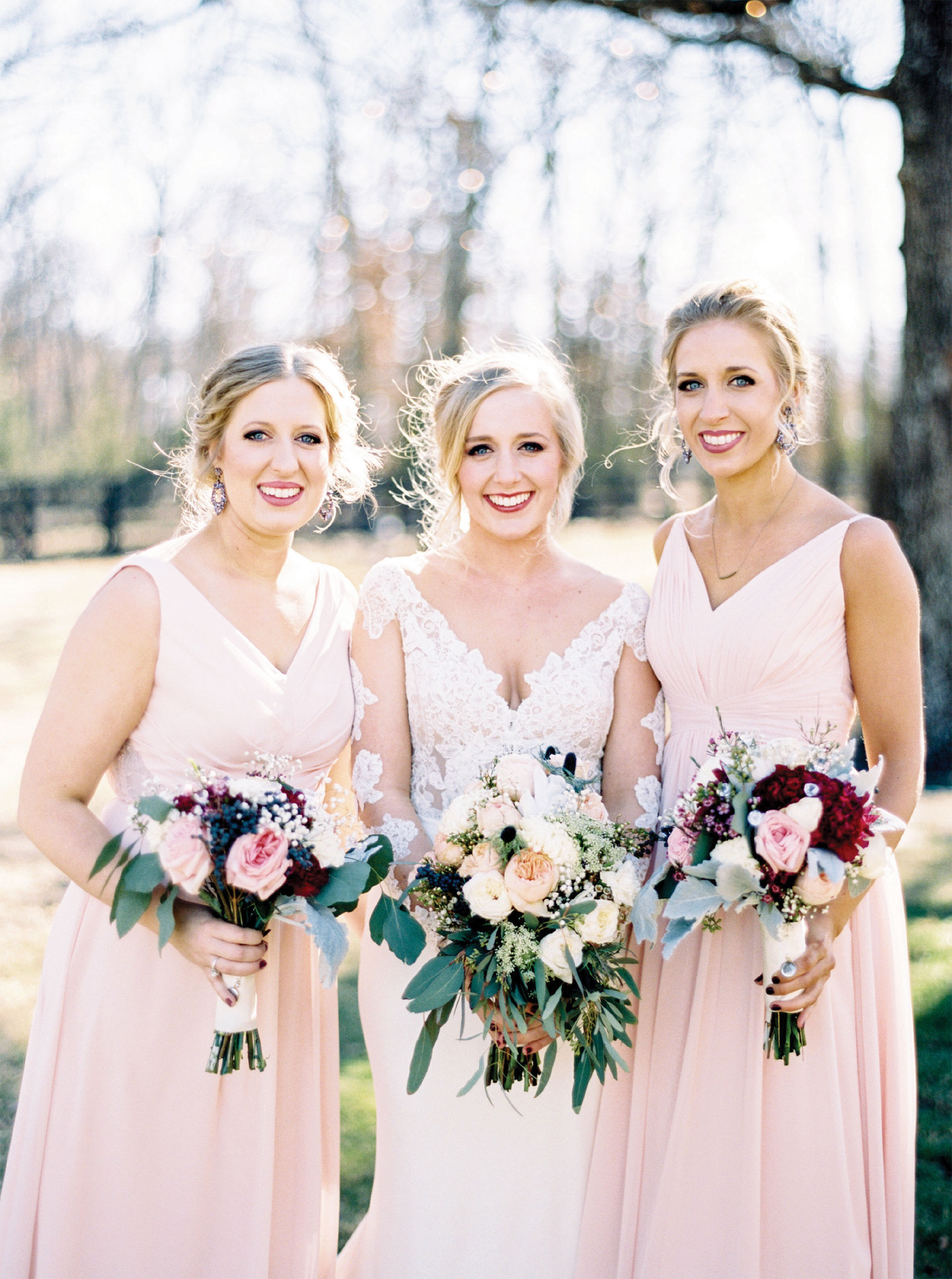 Three Brides in Dresses Holding Flowers for Photo
